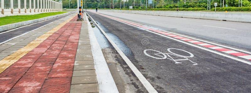 与标志的柏油路和自行车车道 免版税库存照片