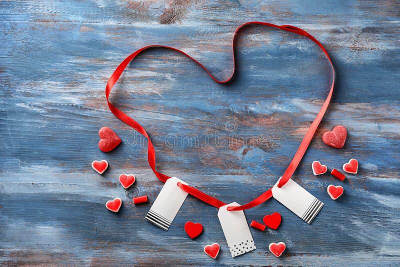 与标记和果冻糖果的心形的丝带在颜色木背景 免版税库存照片