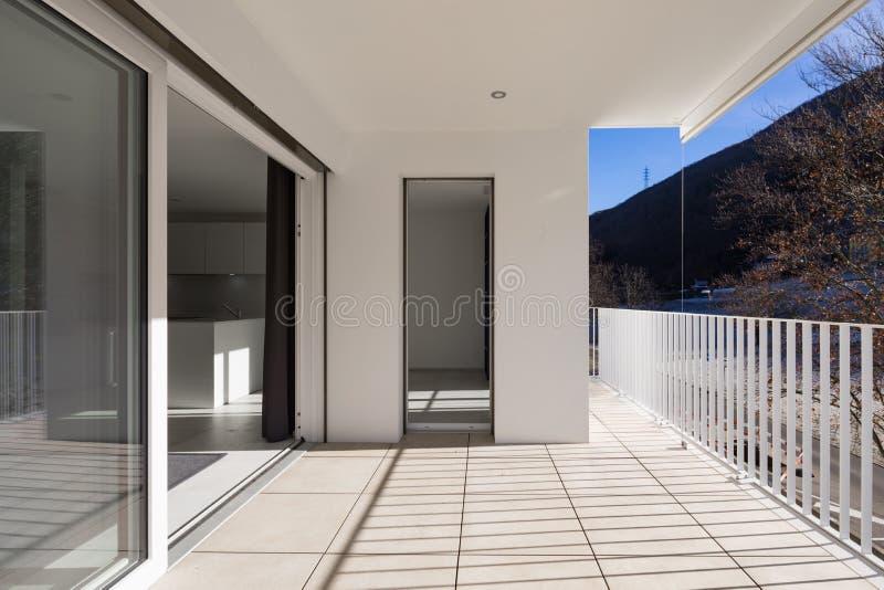 与栏杆的现代房子大阳台 免版税库存照片