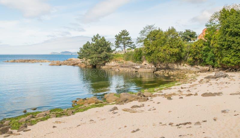 与树和岩石的海滩在西班牙 免版税库存照片