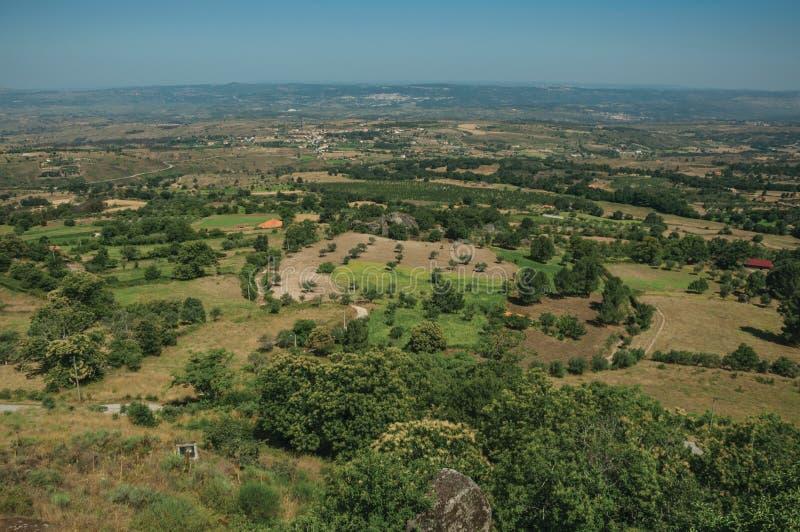 与树和村庄屋顶的乡下风景 图库摄影