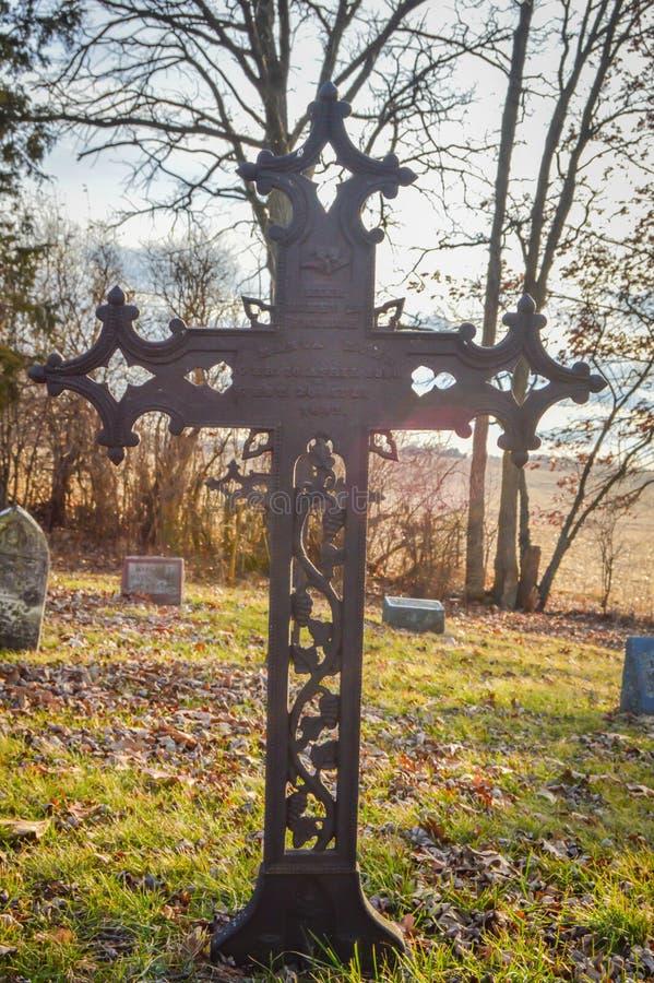 与树枝的生锈的十字架在公墓 免版税库存照片