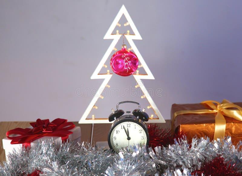 与树的圣诞节在桌上的构成和时钟 免版税库存图片