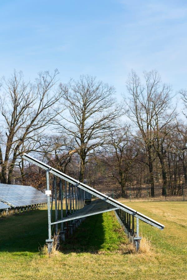 与树的蓝色太阳电池板photovoltaics发电站在背景中 免版税图库摄影