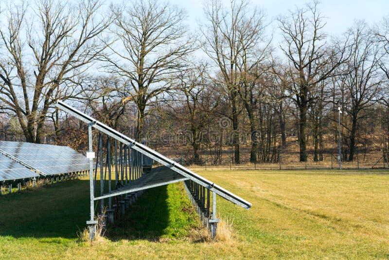 与树的蓝色太阳电池板photovoltaics发电站在背景中 库存照片