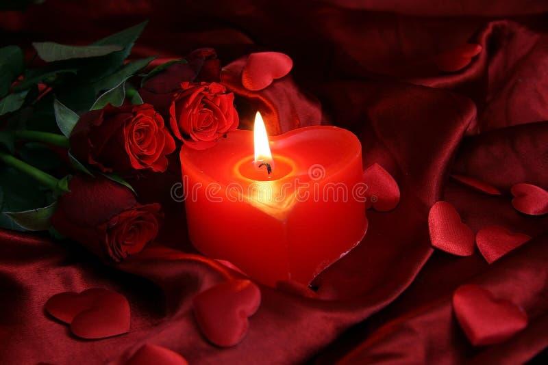 与树红色玫瑰的心脏蜡烛 免版税库存照片
