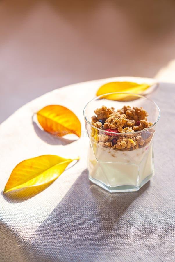 与格兰诺拉麦片、干莓果在玻璃和黄色叶子的酸奶 与土气样式桌布的灰色背景 顶视图拷贝空间 库存图片