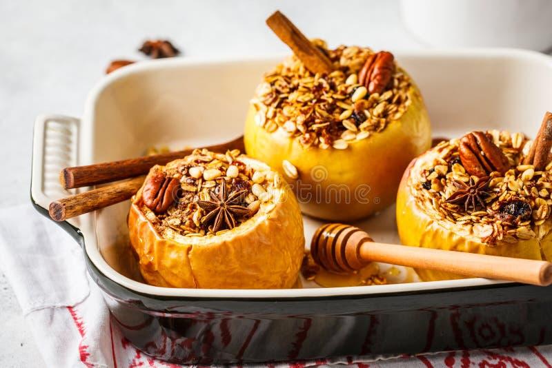 与格兰诺拉麦片、蔓越桔、坚果和蜂蜜的被烘烤的苹果在烤箱盘 免版税图库摄影