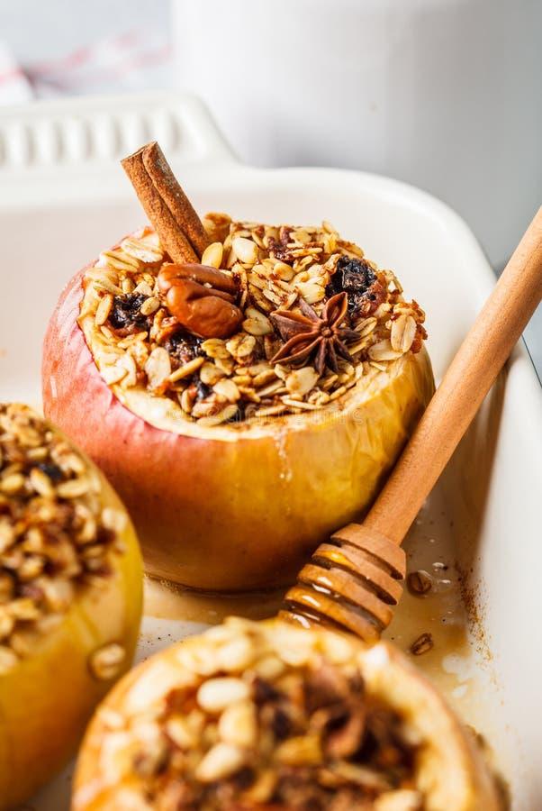 与格兰诺拉麦片、蔓越桔、坚果和蜂蜜的被烘烤的苹果在烤箱盘 库存照片