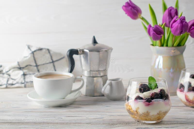 与格兰诺拉麦片、酸奶、咖啡和紫色郁金香花束的新鲜和健康早餐 图库摄影