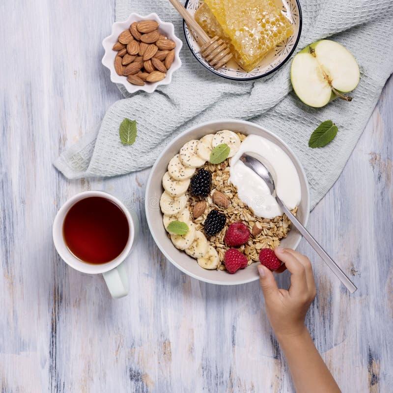 与格兰诺拉麦片的健康早餐、莓果、蜂窝和酸奶和一杯茶,儿童的rasbberry手的藏品 免版税库存图片