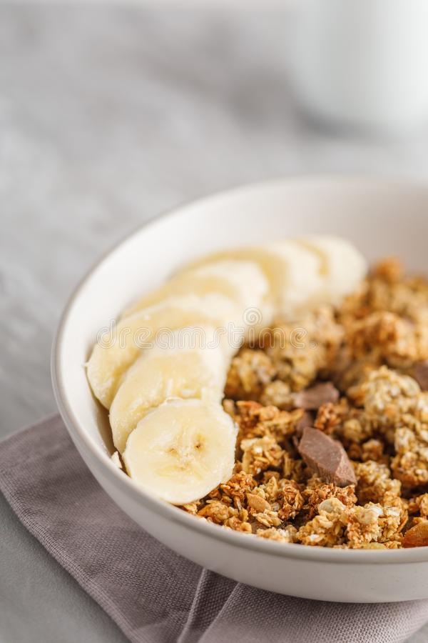 与格兰诺拉麦片的早餐用香蕉 巧克力和瓶子片断在背景的格兰诺拉麦片 免版税库存照片