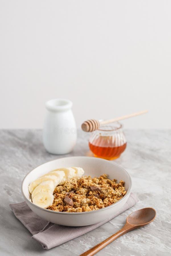 与格兰诺拉麦片的早餐用香蕉 瓶子在背景的蜂蜜 库存图片