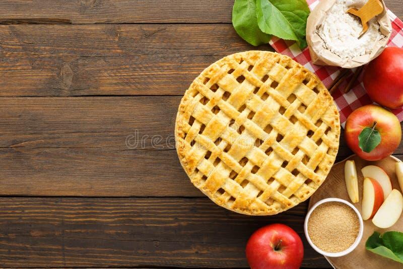 与格子上面的在木桌上的苹果饼和成份 库存照片