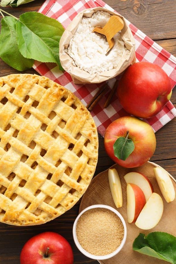 与格子上面的在木桌上的苹果饼和成份 库存图片