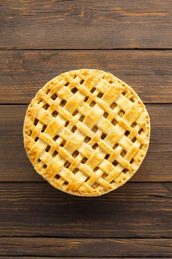 与格子上面的自创苹果饼在棕色木背景 免版税库存照片