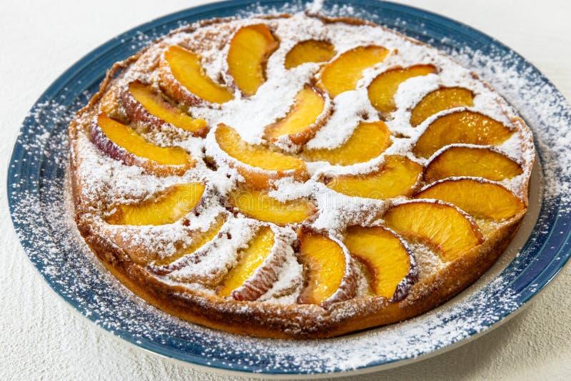 与桃子切片的自创蛋糕在板材 免版税图库摄影