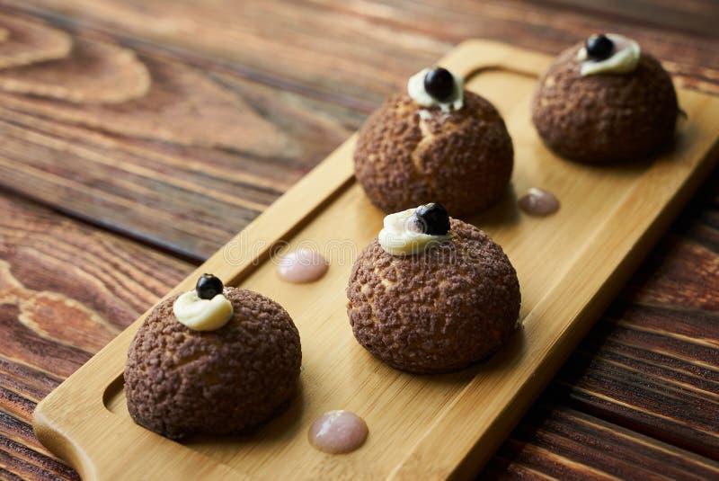 与桃子紫罗兰的可口白色巧克力profiteroles 免版税库存图片
