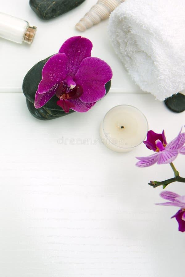 与桃红色兰花、黑石头和腌制槽用食盐的温泉设置在木背景 免版税库存照片
