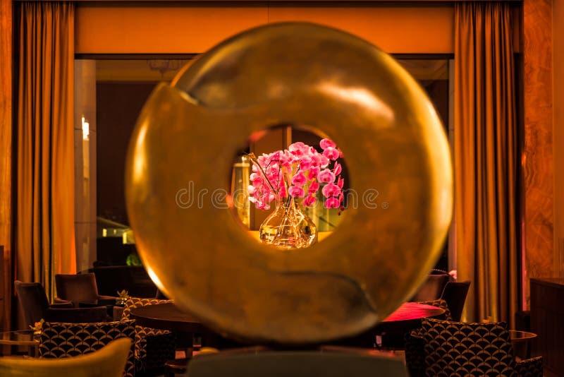 与桃红色兰花的圆的雕塑在背景中在豪华休息室 库存照片