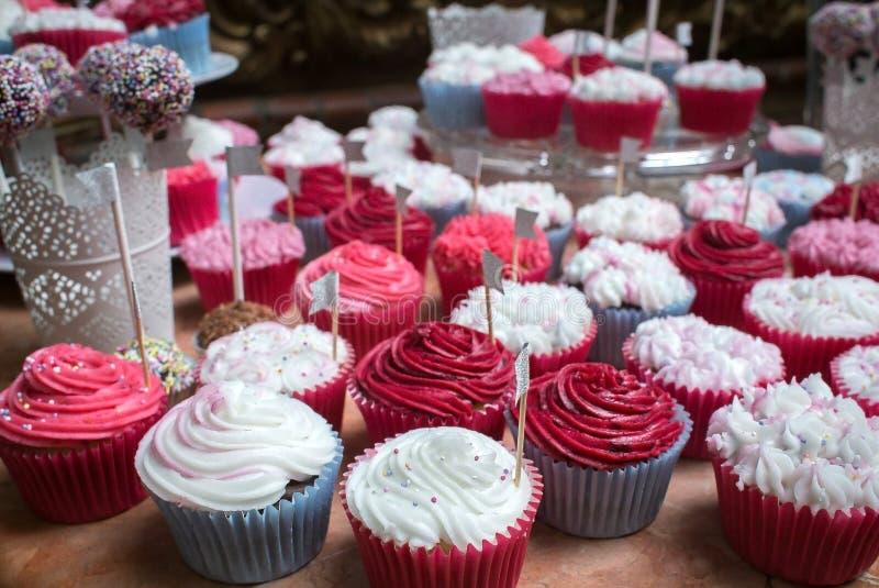 与桃红色和白色结霜的明亮的杯形蛋糕在宴会 免版税库存图片