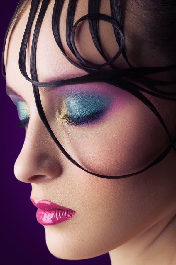 与桃红色和蓝色构成的年轻美好的在她的面孔的时装模特儿和发型 免版税库存图片