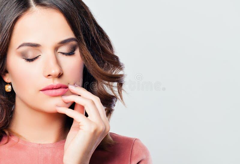 与桃红色嘴唇构成和被修剪的手的完善的妇女面孔 免版税库存图片