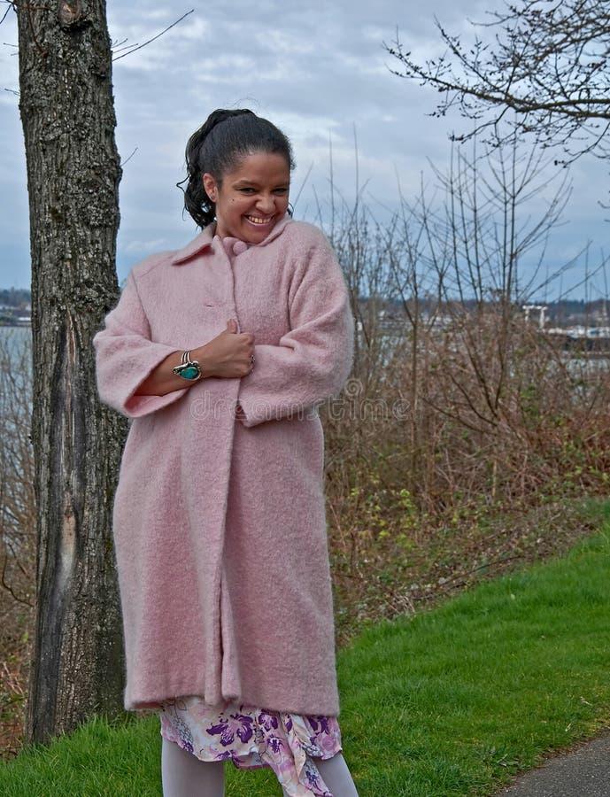 与桃红色外套的Multi_Ethnic妇女嬉戏的外部 图库摄影