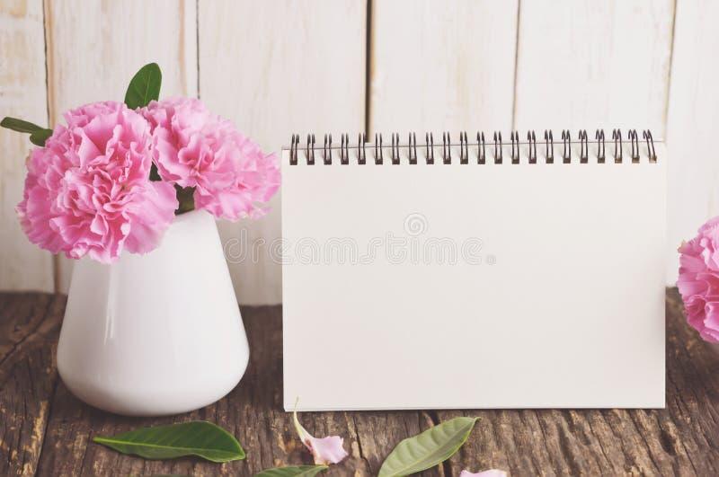 与桃红色康乃馨花的空白的桌面日历 免版税库存照片