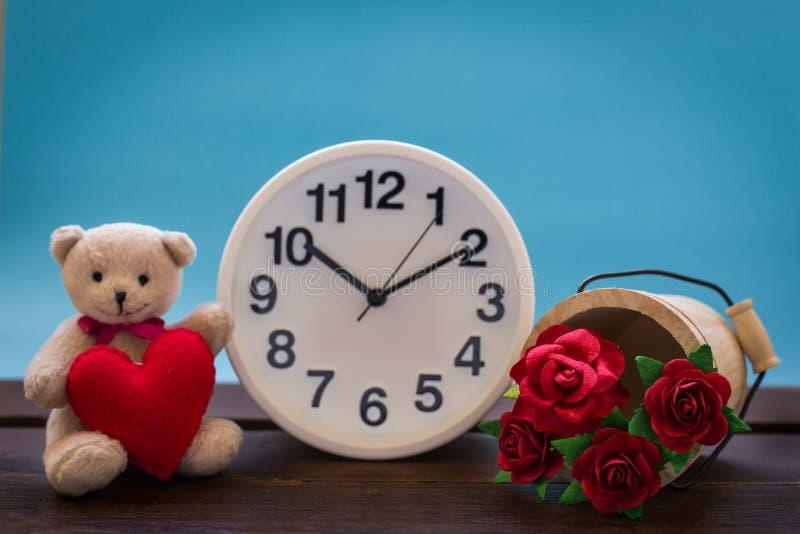 与桃红色心脏和时钟装饰的玩具熊在木桌上 免版税库存照片