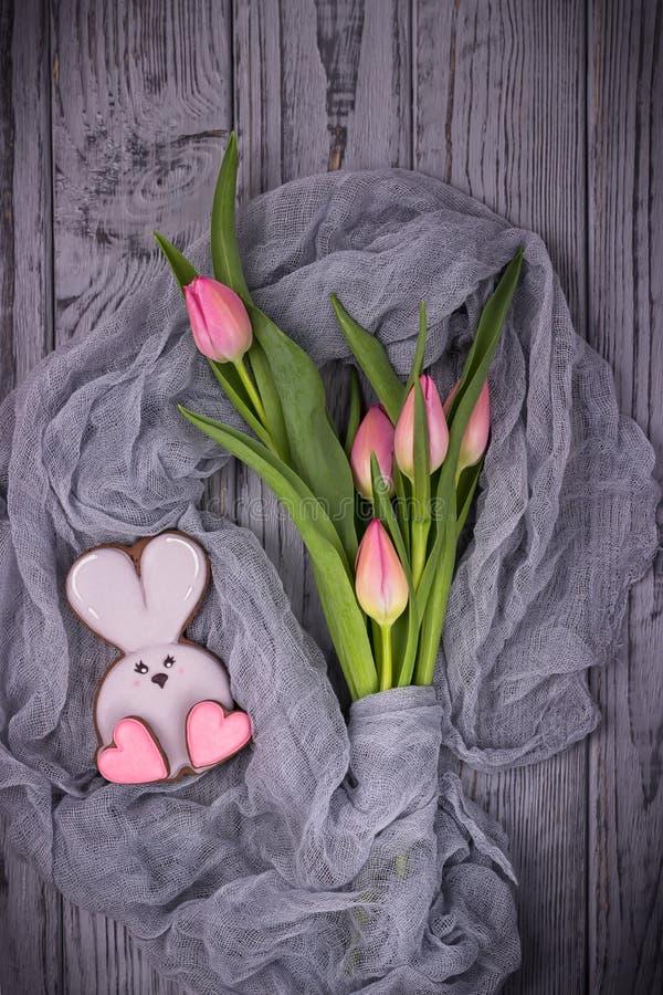与桃红色心脏的姜饼兔子和在木背景的桃红色郁金香 顶视图,自由空间 图库摄影