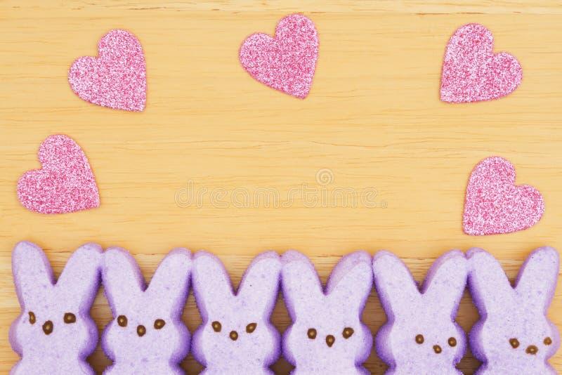 与桃红色心脏的紫色糖果兔宝宝在织地不很细木背景 免版税库存照片