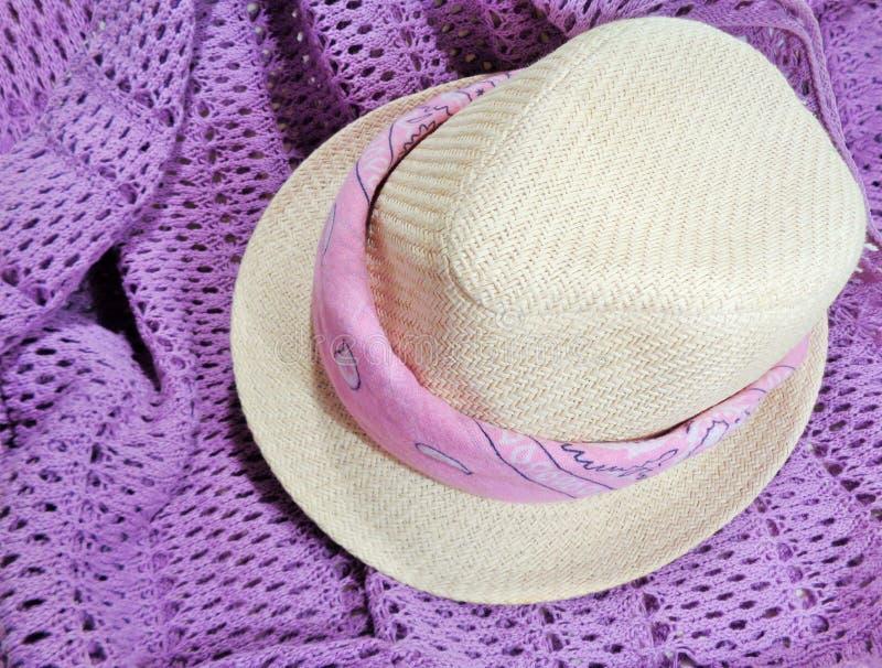 与桃红色方巾的秸杆浅顶软呢帽在紫色编织毛线衣 库存照片