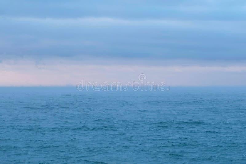 与桃红色日落和蓝色云彩的美好的海景 风平浪静 免版税库存图片