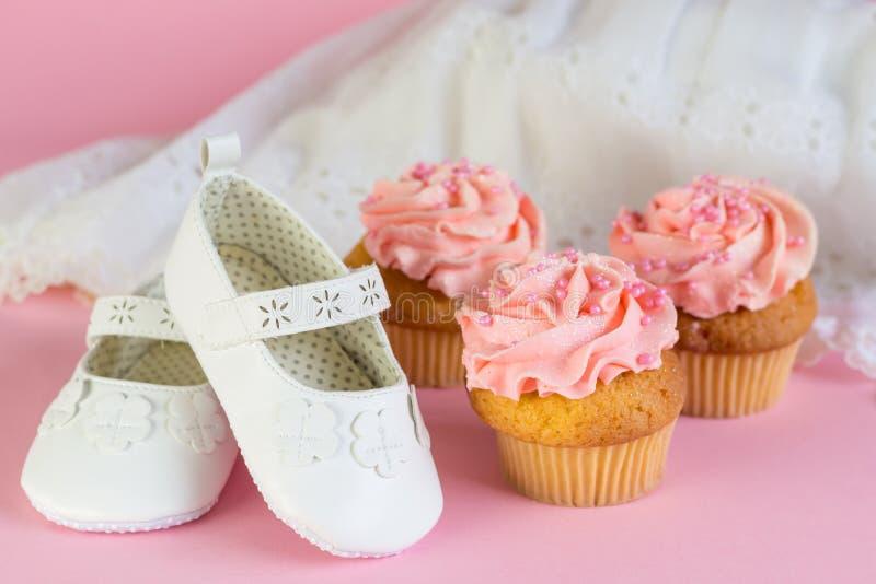 与桃红色杯子蛋糕和丝毫的洗礼或生日女孩邀请 库存照片