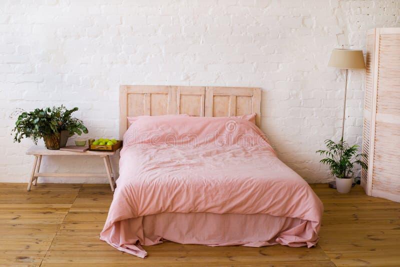 与桃红色枕头和桃红色盖子的空的床在卧室 免版税库存图片