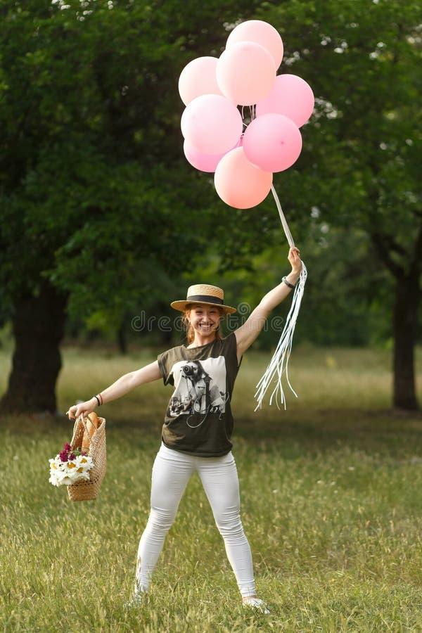 与桃红色气球的女孩跳舞在公园 女孩野餐党 免版税库存照片