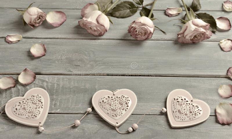 与桃红色玫瑰和心脏的浪漫爱背景在葡萄酒 库存照片