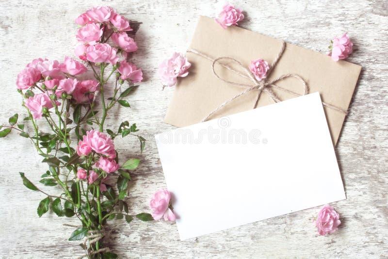 与桃红色玫瑰的空白的白色贺卡开花花束 图库摄影