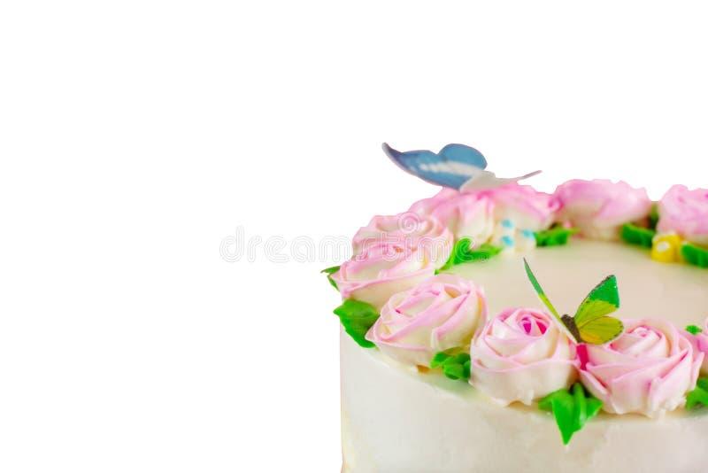 与桃红色玫瑰的黄油奶油色池塘蛋糕,绿色事假和蝴蝶装饰隔绝 免版税库存图片