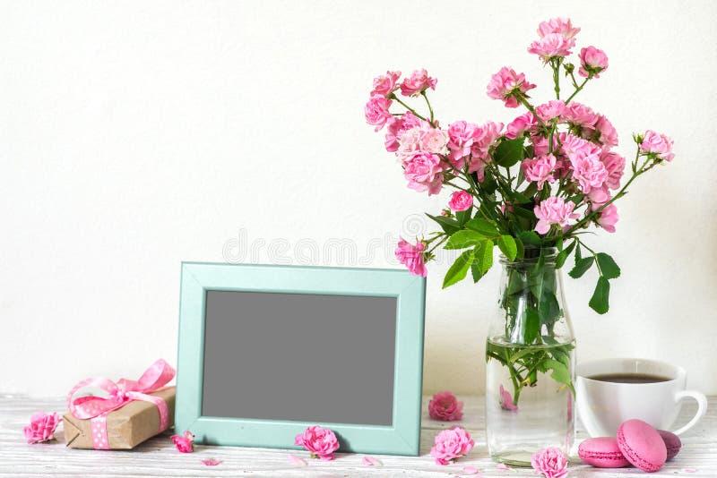 与桃红色玫瑰花、咖啡杯、蛋白杏仁饼干和礼物盒美丽的花束的空白的照片框架  库存图片