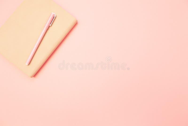 与桃红色笔的米黄日志在淡色千福年的桃红色纸背景 教育的概念,写博克 顶视图 平的位置 库存图片