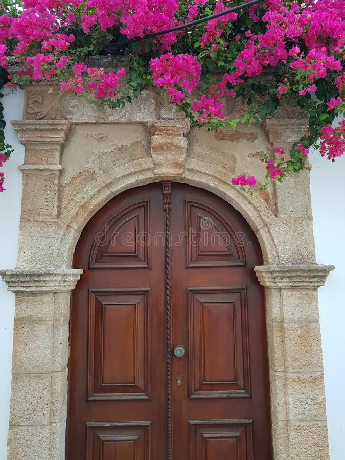 与桃红色红色花的破旧的木门在中世纪sentury样式 免版税库存照片