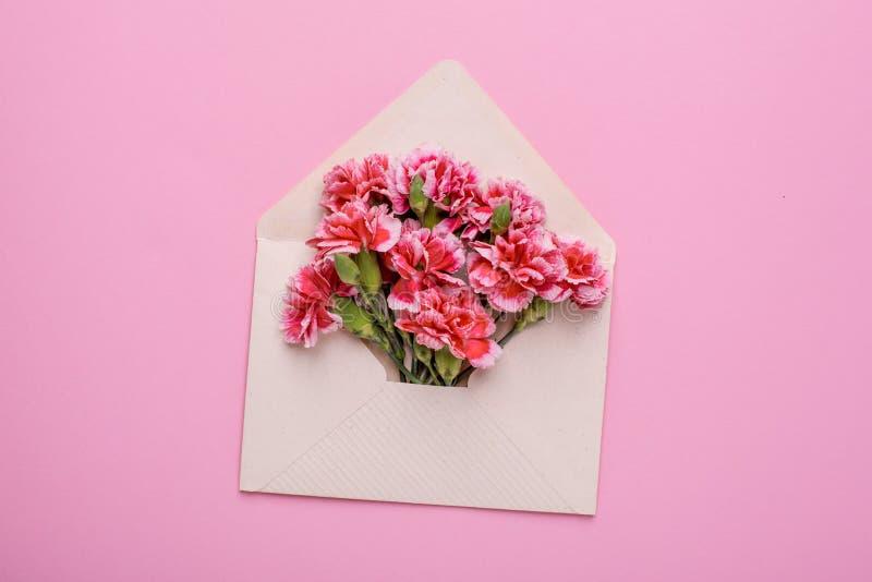 与桃红色花的信封在桃红色背景 免版税库存图片