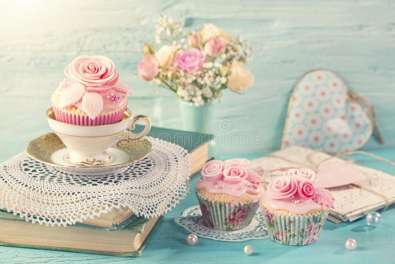 与桃红色花的杯形蛋糕 免版税库存照片