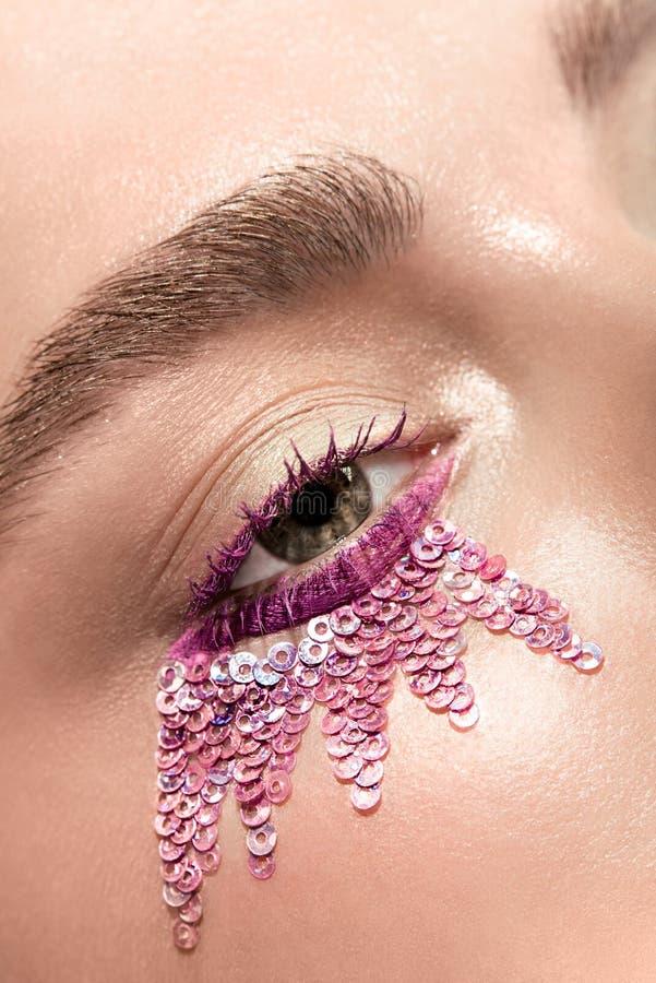与桃红色衣服饰物之小金属片的妇女眼睛 免版税库存图片