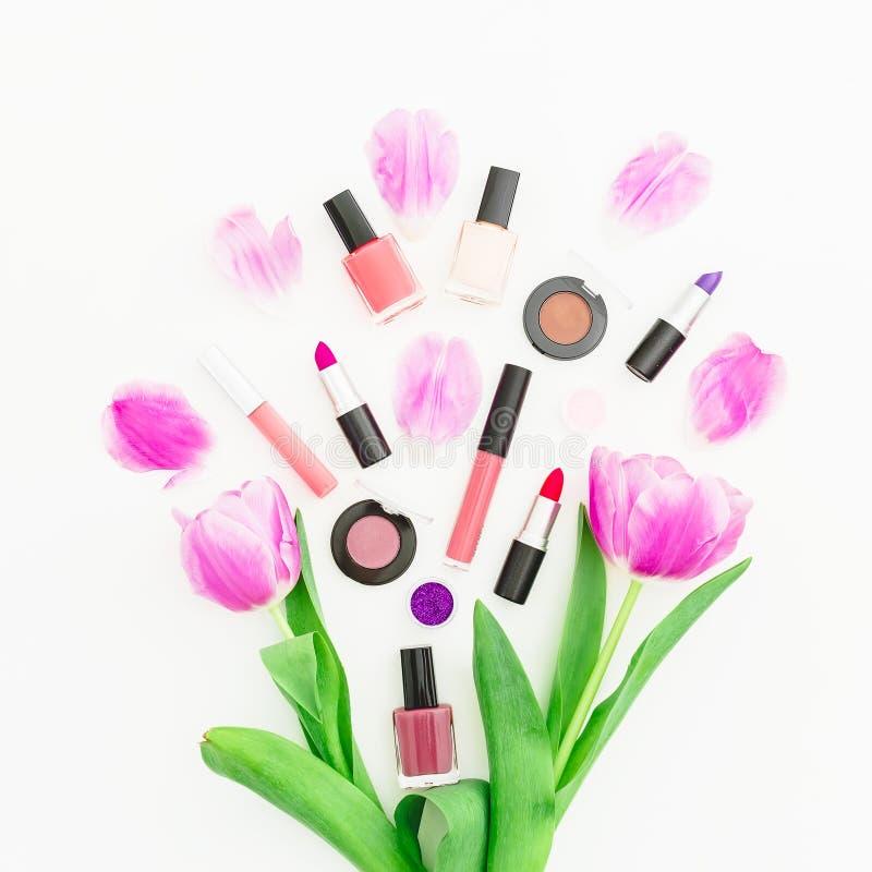 与桃红色郁金香花束的秀丽在白色背景的构成和化妆用品 顶视图 平的位置 家庭女性书桌 库存图片