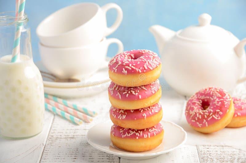 与桃红色釉的被烘烤的油炸圈饼和洒 免版税库存照片