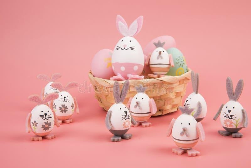 与桃红色题材的复活节彩蛋在篮子 鸡蛋装饰象使用与另一个兔宝宝的一个逗人喜爱的兔宝宝,在桃红色背景 免版税库存图片