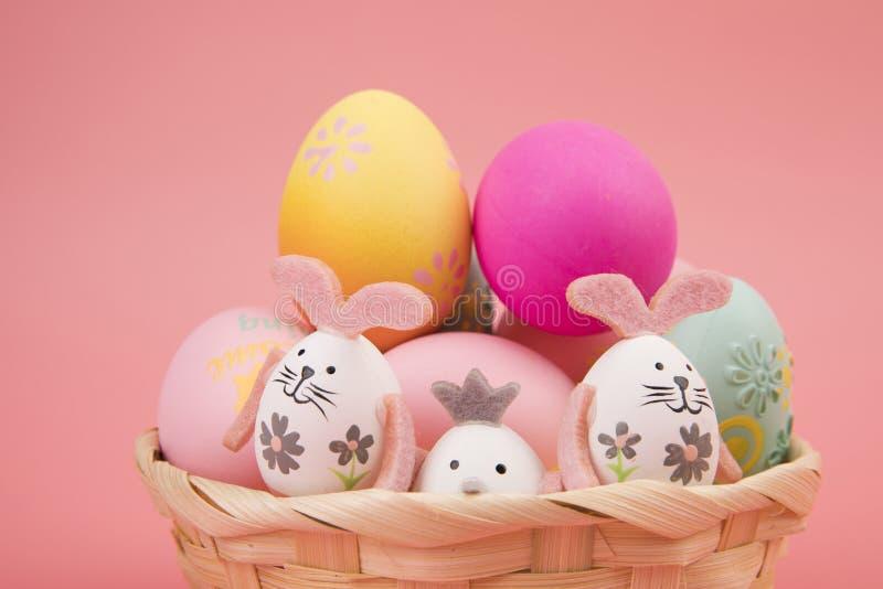 与桃红色题材的复活节彩蛋在篮子 鸡蛋装饰象使用与另一个兔宝宝的一个逗人喜爱的兔宝宝,在桃红色背景 库存图片